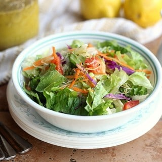 A bowl of salad and vegetables sitting on a table with two lemons, plates, silverware, and a jar of salad dressing.