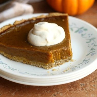 A slice of pumpkin pie sitting on a stack of plates, topped with whipped cream.