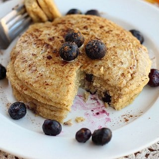 Pancakes with blueberries and melted coconut oil on a white plate.