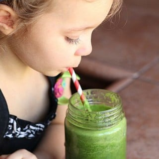 Child drinking green smoothie with a red and white straw.