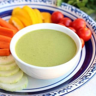 White bowl with green cilantro dressing surrounded by tomatoes, carrots, cucumbers, and bell pepper.