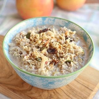 Blue bowl filled with oats, pumpkin seeds, coconut, and raisins, all topped with milk.