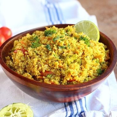 Yellow quinoa with vegetables in a brown bowl.
