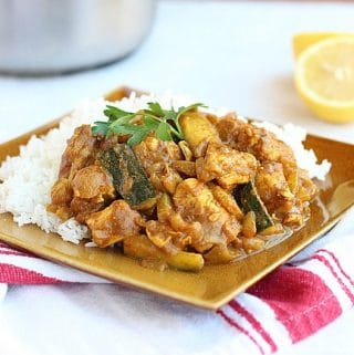 Indian chicken curry and white rice on a brown plate.