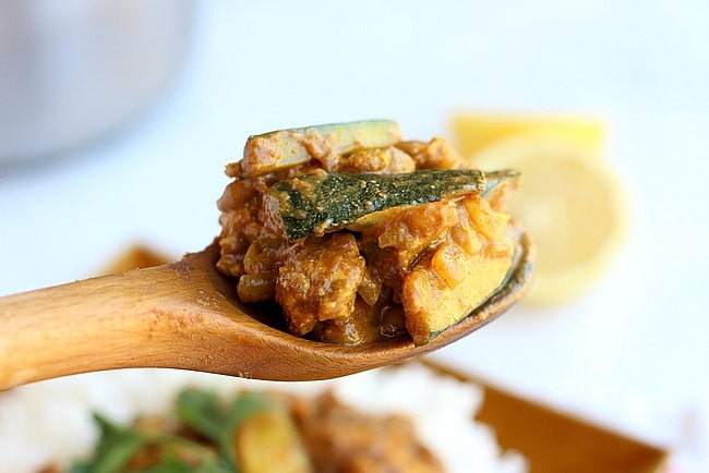 Chicken curry and zucchini on a wooden spoon.