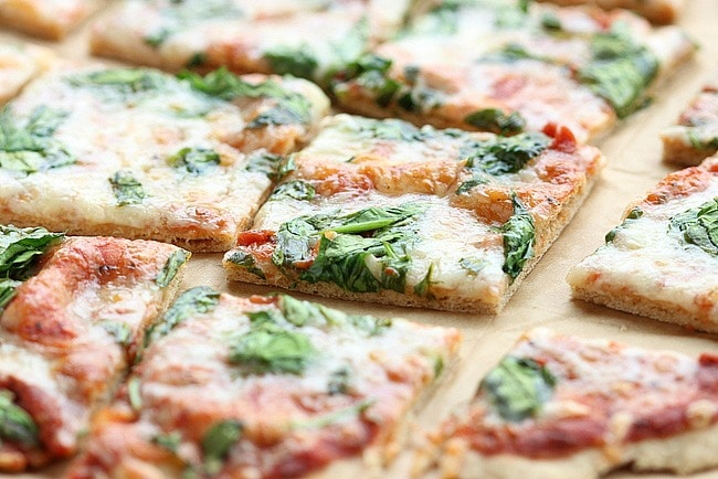 Close-up of a piece of thin crust pizza topped with cheese and spinach.
