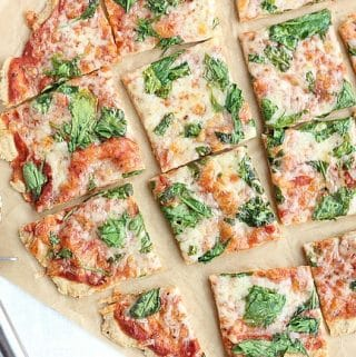 Overhead shot of thin crust pizza cut into squares.