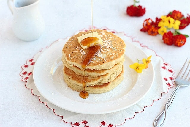 Gluten-free pancakes topped with butter and maple syrup.
