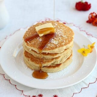 Stack of gluten-free pancakes atop a white plate.