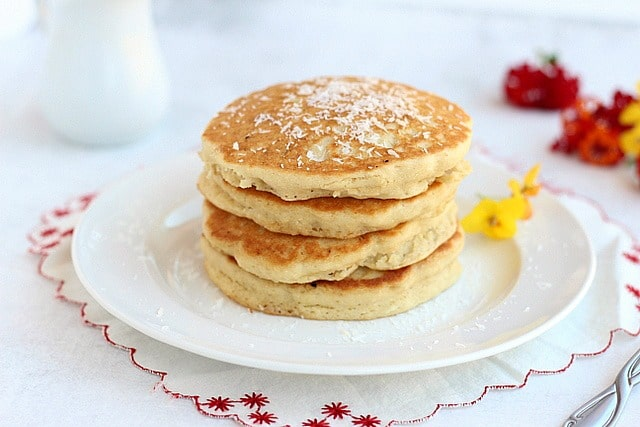 Stack of vanilla coconut pancakes on a white plate.