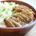 Teriyaki chicken bowl with rice and scallions.