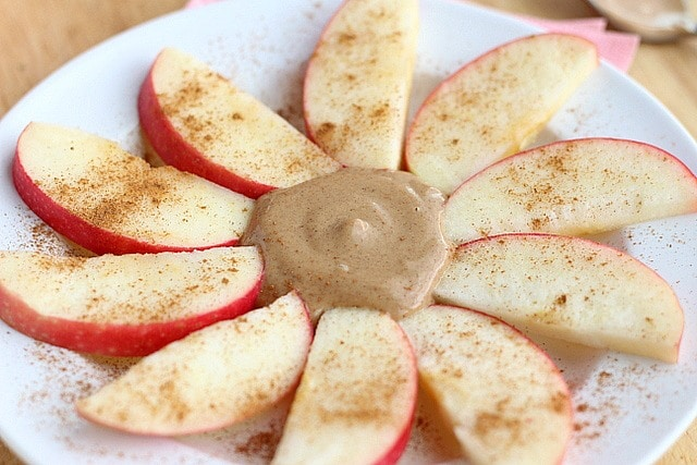 Peanut butter dip surrounded by apples