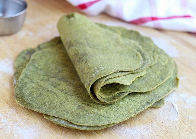 Stack of spinach tortillas on a plate.